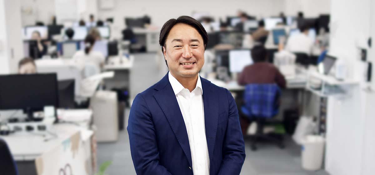 大阪本社を背景にした代表取締役 辻 友崇 近影